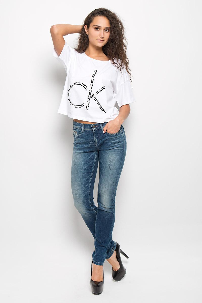Футболка7038Стильная женская футболка Calvin Klein Jeans изготовлена из эластичного хлопка. Материал изделия мягкий, тактильно приятный, не сковывает движения и хорошо пропускает воздух, обеспечивая комфорт при носке. Укороченная модель футболки с круглым вырезом горловины и короткими рукавами имеет свободный силуэт. Изделие оформлено аппликацией в виде фирменного логотипа. Сзади на плечевом шве находится принтовая надпись, содержащая название бренда. Высокое качество, актуальный дизайн и расцветка придают изделию неповторимый стиль и индивидуальность. Футболка займет достойное место в вашем гардеробе!