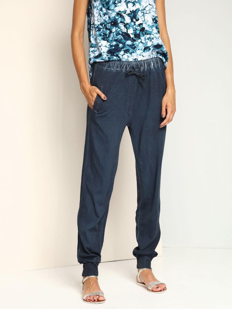 SSP2288NIСтильные женские брюки с заниженной ластовицей выполнены из натурального хлопка. Модель в поясе дополнена широкой эластичной резинкой и утягивающим шнурком, оформлена имитацией ширинки. Спереди предусмотрены два втачных кармана. Низ брючин дополнен широкими трикотажными манжетами.