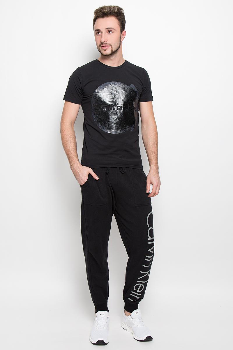 NM1263E_001Стильная мужская футболка Calvin Klein Jeans, выполненная из натурального хлопка с добавлением эластана, обладает высокой теплопроводностью, воздухопроницаемостью и гигроскопичностью. Модель с короткими рукавами и круглым вырезом горловины - идеальный вариант для создания модного современного образа. Футболка оформлена крупным контрастным принтом с логотипом Calvin Klein.