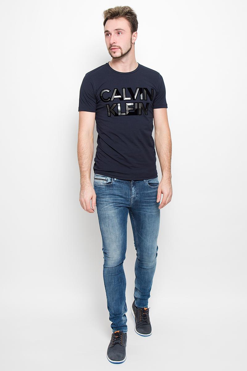ФутболкаJ30J300562_402Мужская футболка Calvin Klein Jeans, выполненная из эластичного хлопка, идеально подойдет для повседневной носки. Футболка с круглым вырезом горловины и короткими рукавами имеет полуприлегающий силуэт. Спереди изделие украшено фактурной надписью с названием бренда.
