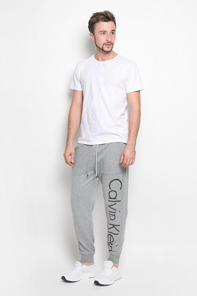 Брюки для домаNM1263E_001Мужские брюки для дома Calvin Klein Underwear выполнены из хлопка с добавлением полиэстера. Изнаночная сторона изделия с теплым начесом. Эластичный пояс с затягивающимся шнурком позволяет отрегулировать посадку точно по фигуре. Спереди расположены два втачных кармана. Низ брючин дополнен трикотажными манжетами. Оформлено изделие термоаппликацией в виде надписи.