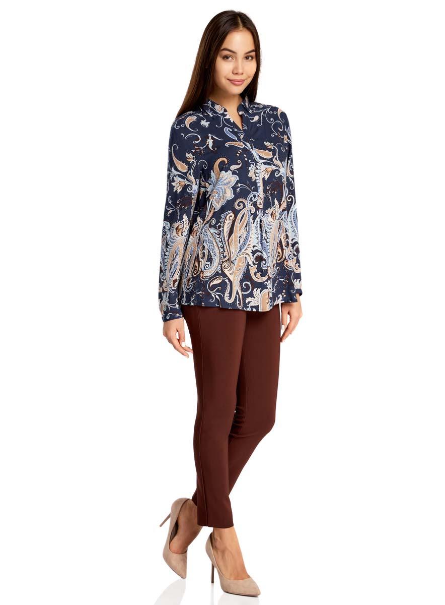 Блузка21411144-4/26346/5762EОригинальная женская блузка oodji Collection выполнена из качественной вискозы. Модель свободного кроя с отложным воротником и длинными рукавами застегивается спереди на пуговицы скрытые планкой. Манжеты рукавов также имеют застежки-пуговицы. Спереди модель дополнена элегантным V-образным вырезом. Оформлена блузка стильным принтом с узорами. Спинка модели немного удлинена.