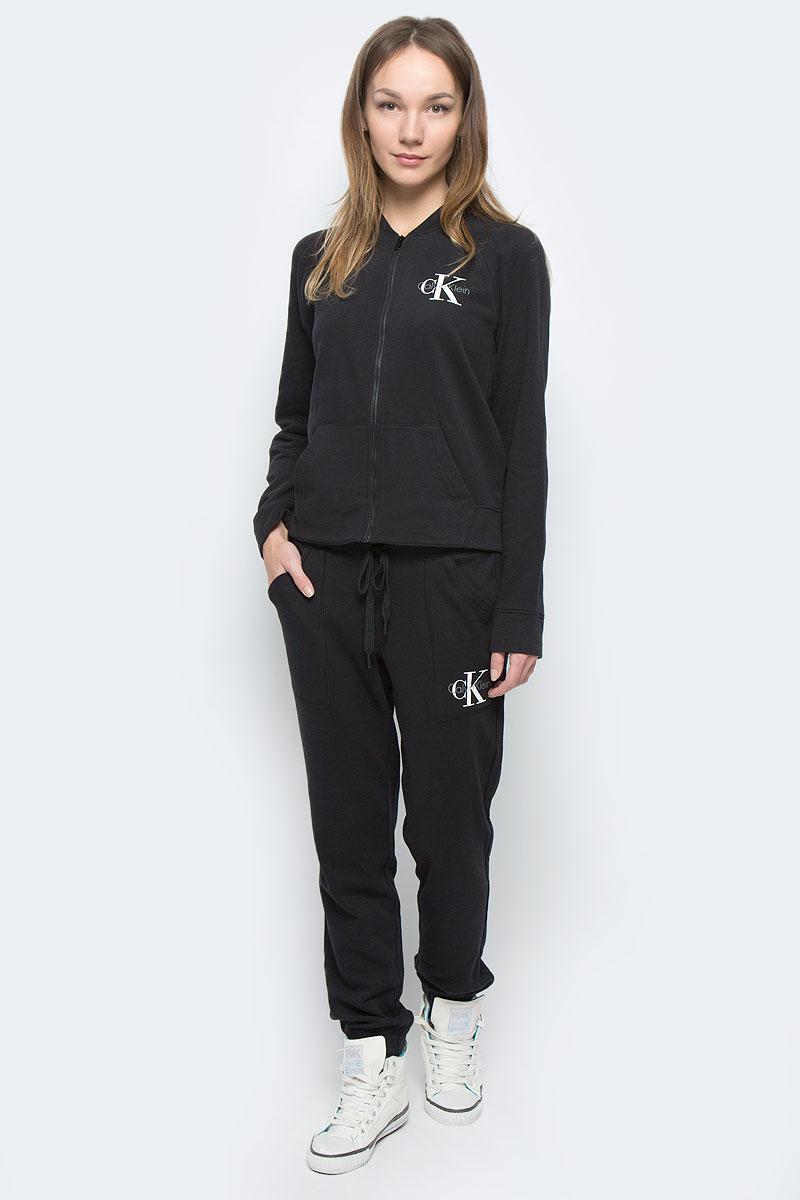 БрюкиQS5537E_001Женские брюки Calvin Klein Underwear выполнены из хлопка с добавлением полиэстера. Модель по поясу дополнена эластичной резинкой и шнурком-кулиской. Спереди расположено два втачных кармана с косыми срезами. Низ брючин присобран на резинку. Брюки оформлены термоаппликацией в виде названия бренда.