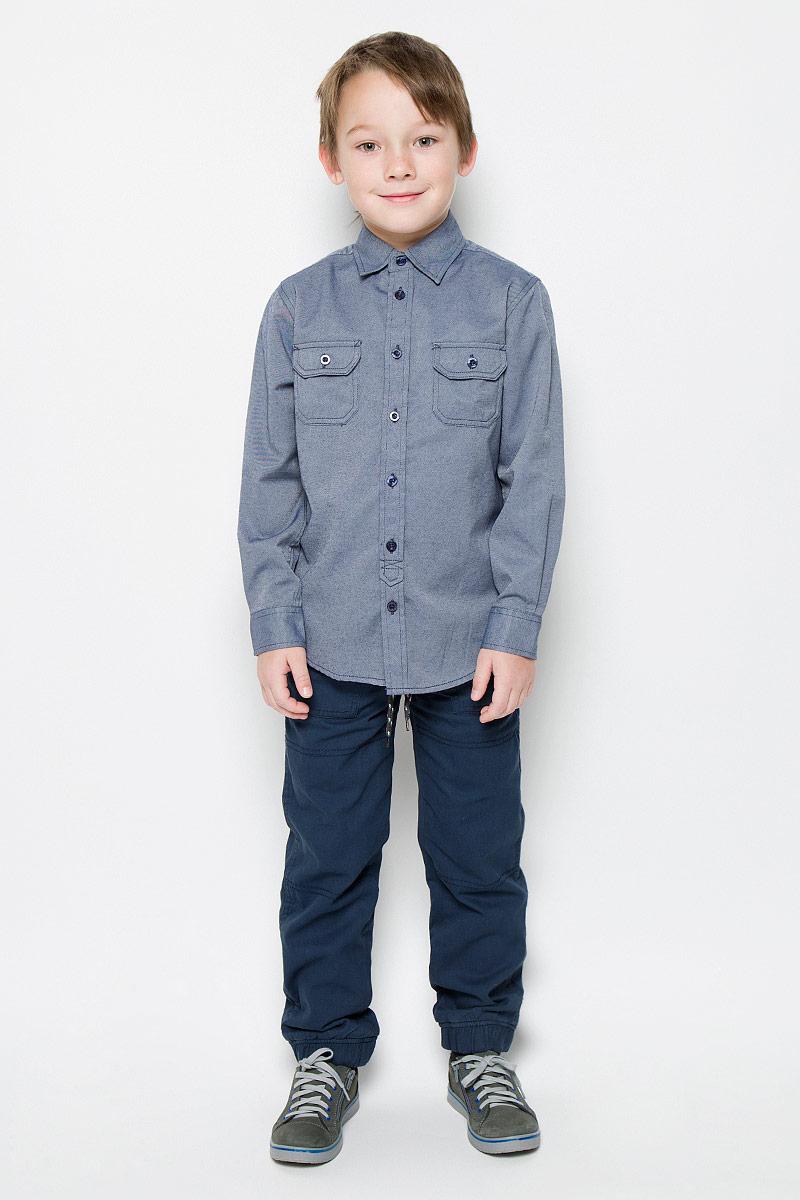 H-812/195-6415Рубашка для мальчика Sela выполнена из хлопка с добавлением полиэстера. Рубашка с длинными рукавами и отложным воротником застегивается на пуговицы спереди. Манжеты рукавов также застегиваются на пуговицы. На груди расположены два накладных кармана с клапанами на пуговицах.