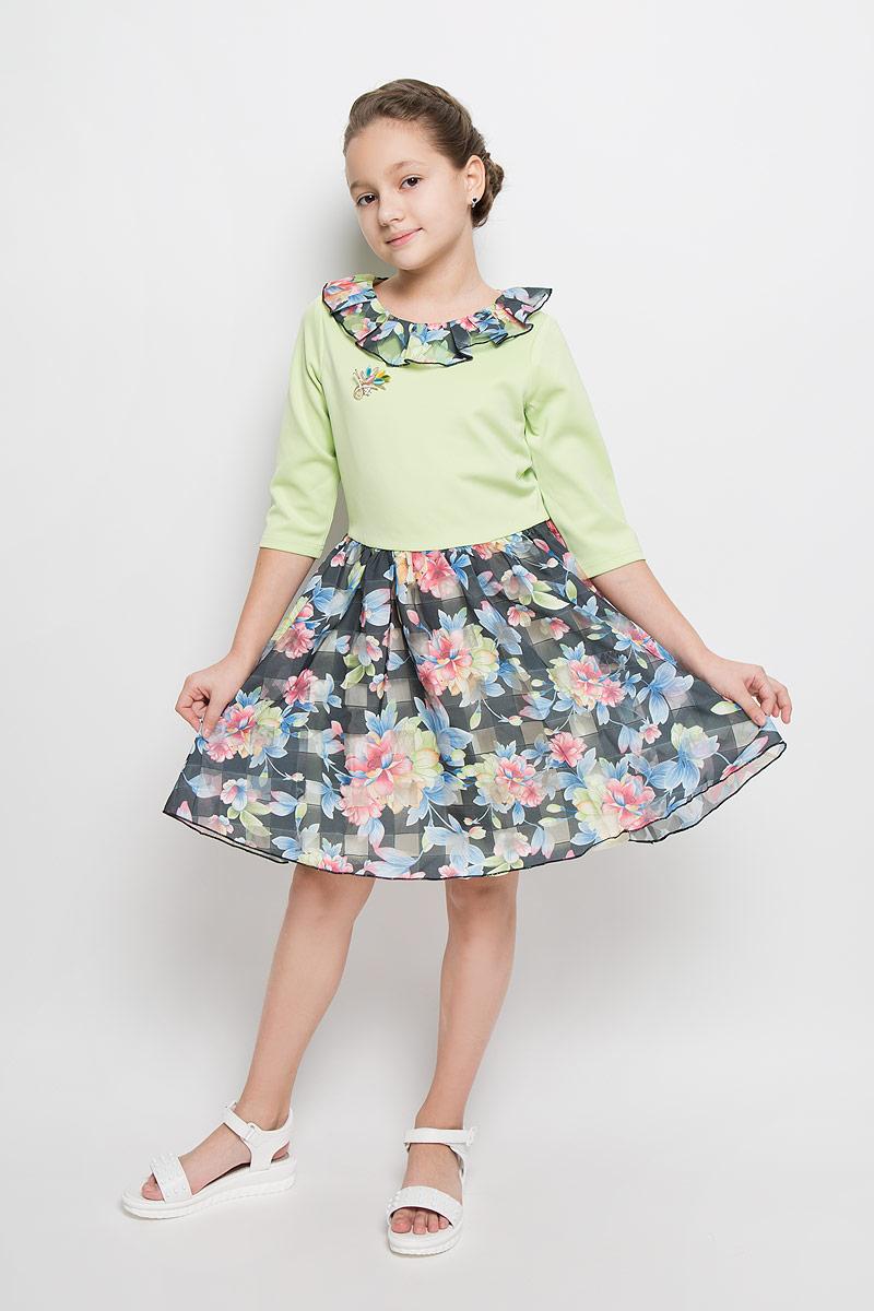 ND6506-77Платье для девочки Nota Bene выполнено из 100% полиэстера и дополнено подкладкой из натурального хлопка. Платье-миди с круглым вырезом горловины и рукавами длинной 3/4 застегивается на потайную застежку-молнию расположенную в среднем шве спинки. Юбка модели дополнена мягкими складками и оформлена цветочным принтом. Платье по горловине дополнено оборкой и декоративной брошью.