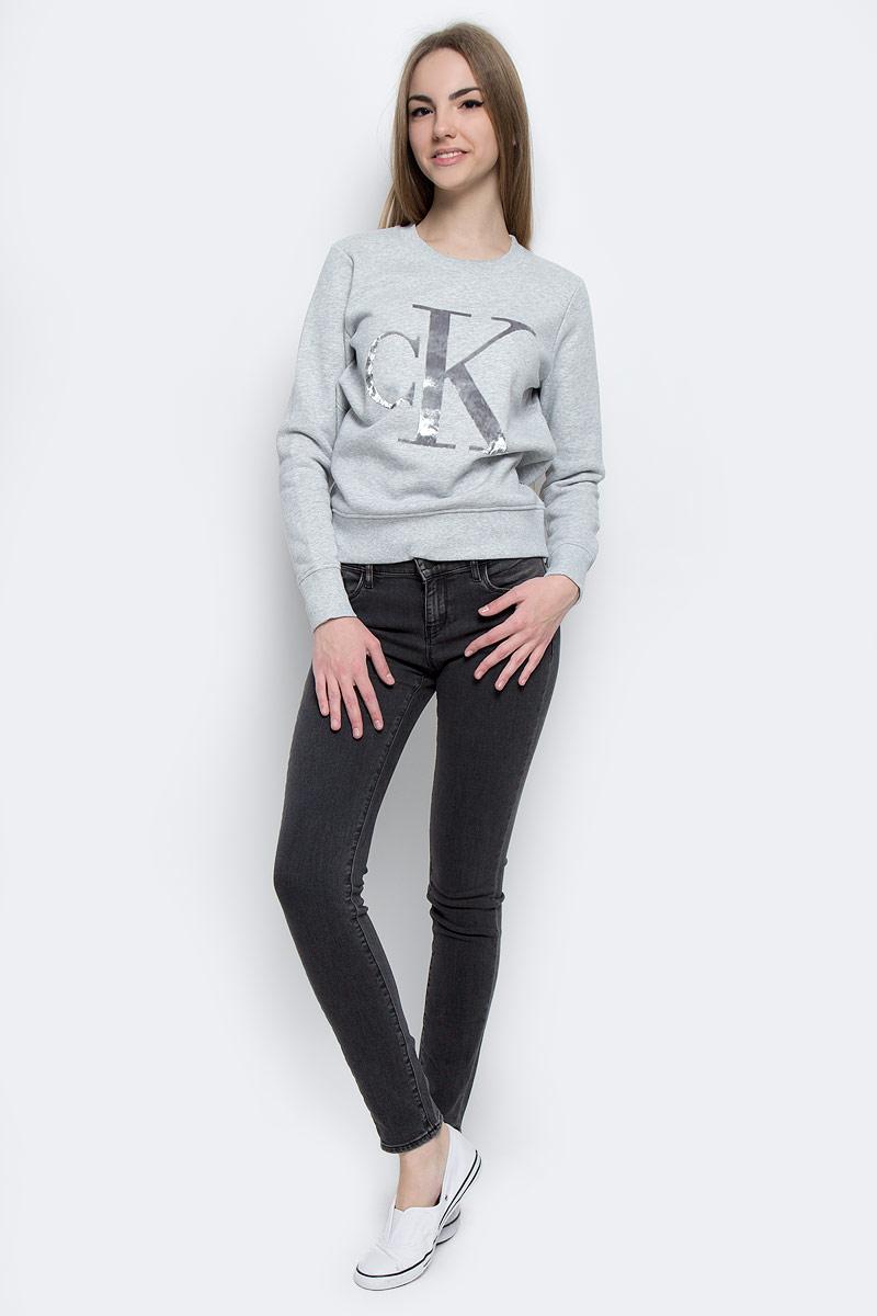 J20J201084_0380Стильная женская толстовка Calvin Klein Jeans изготовлена из натурального хлопка с добавлением полиэстера. Модель с круглым вырезом горловины и длинными рукавами с внутренней стороны выполнена на теплом флисе. Горловина, манжеты рукавов и низ толстовки оформлены трикотажной резинкой. Спереди толстовка дополнена стильным принтом с логотипом бренда.