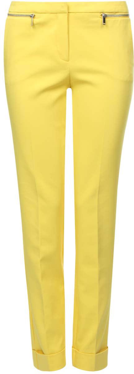 11701033/35589/5100NСтильные женские брюки oodji Ultra выполнены из полиэстера и хлопка с добавлением эластана. Зауженная модель застегивается на молнию, крючок и пуговицу. Спереди расположены два втачных кармана. Брючины дополнены отворотами. Изделие украшено декоративными молниями.