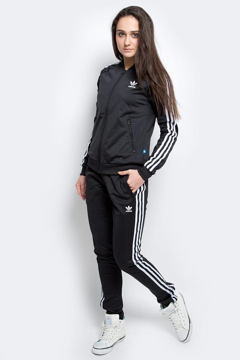 ТолстовкаAJ8432Культовая женская олимпийка - модель из блестящего трикотажа с аутентичными деталями в стиле adidas, такими как рифленый бейсбольный воротник, контрастные три полоски и прорезиненный Трилистник на спине. Рукава-реглан для максимально комфортной посадки. Карманы на лицевой стороне. Классический крой.
