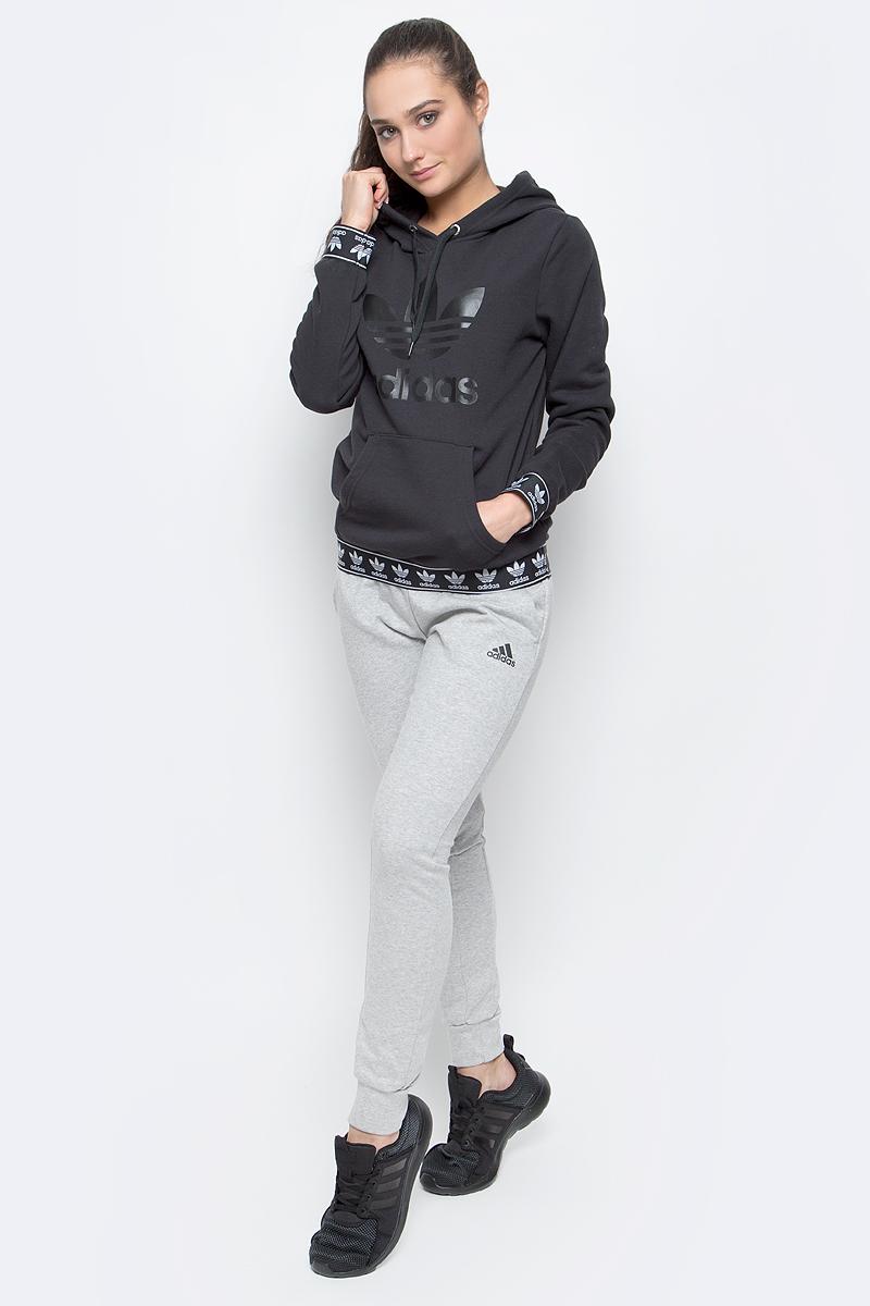 ТолстовкаBJ8307Женская толстовка adidas Logo с длинными рукавами и капюшоном изготовлена из хлопка с добавлением полиэстера. Рукава и низ толстовки дополнены широкими эластичными манжетами с логотипом бренда. Объем капюшона регулируется при помощи шнурка-кулиски. Спереди расположен накладной карман-кенгуру. Толстовка украшена крупным принтом с изображением логотипа adidas на груди.