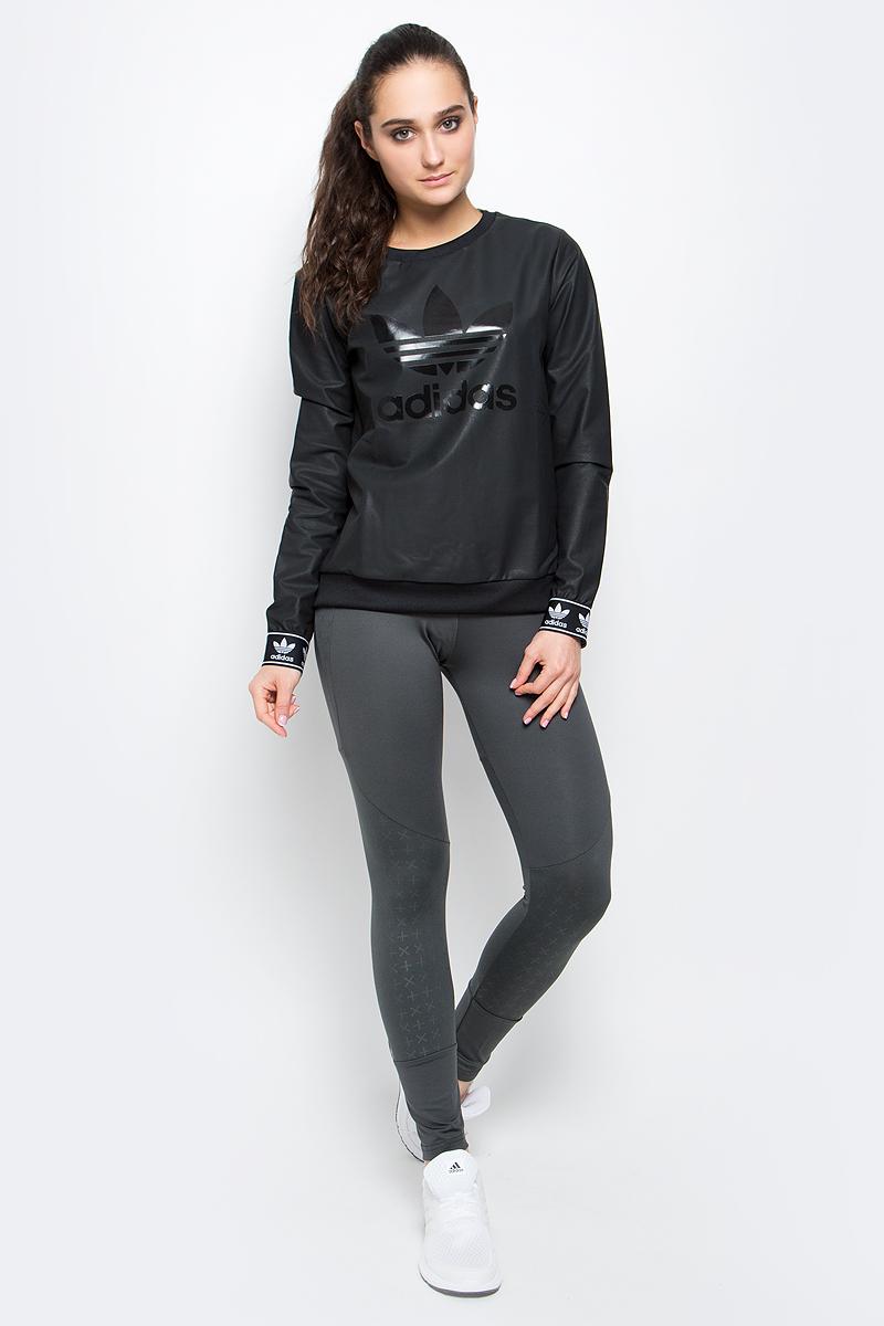 СвитшотBJ8291Женский свитшот adidas Crew Sweater с длинными рукавами и круглым вырезом горловины имеет свободный крой. Свитшот изготовлен из полиэстера с добавлением хлопка и имеет покрытие из полиуретана. Низ и рукава изделия дополнены эластичными манжетами. Спереди свитшот украшен крупным блестящим принтом с логотипом бренда.