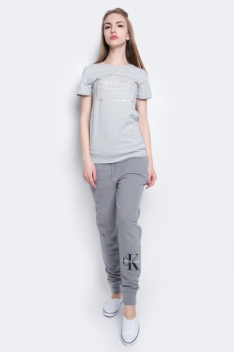J20J205315_0380Женская футболка Calvin Klein Jeans изготовлена из высококачественного эластичного хлопка. Модель с короткими рукавами и круглым вырезом горловины украшена блестящим принтом с логотипом бренда.