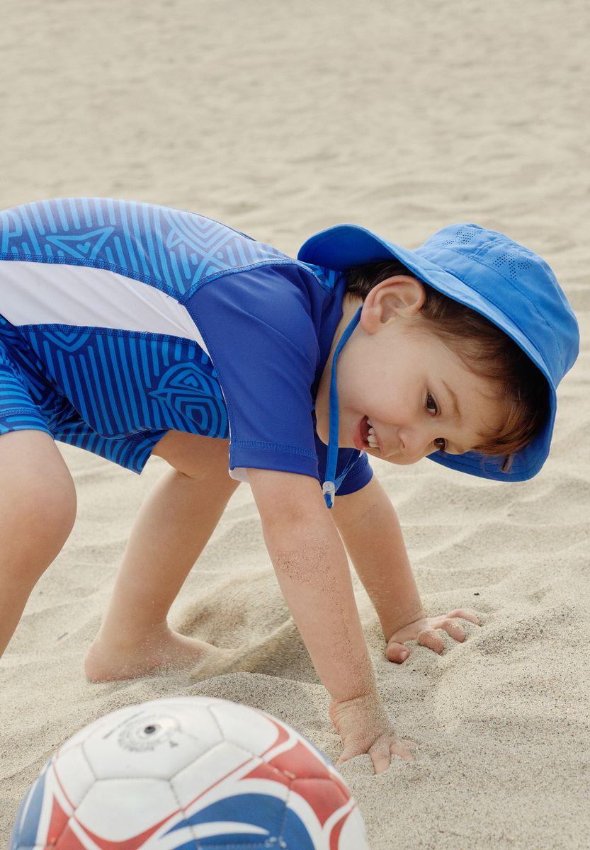 Панама5285310100Защитная панама для малышей и детей постарше с фактором УФ-защиты 50+. Козырек панамы защищает лицо и глаза от вредного ультрафиолета. Изготовлена из дышащего и легкого материала SunProof. Облегченная модель без подкладки, а чтобы ветер не унес эту новую очаровательную панаму, просто завяжите завязки!