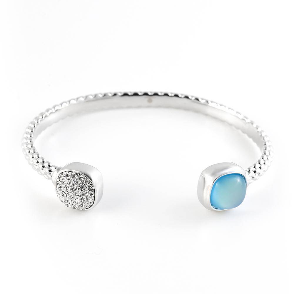 Браслет Selena Medea, цвет: серебряный, голубой. 4007854040078540Стильный браслет Selena Street Fashion изготовленный из гипоаллергенного материала, выполнен из металла c родиевым покрытием. Изящный браслет-дуга универсального размера дополнен круглыми декоративными элементами на концах, инкрустированными стразами и кристаллом Preciosa. Такой оригинальный браслет не оставит равнодушной ни одну любительницу изысканных и необычных украшений, а также позволит с легкостью воплотить самую смелую фантазию и создать собственный, неповторимый образ.