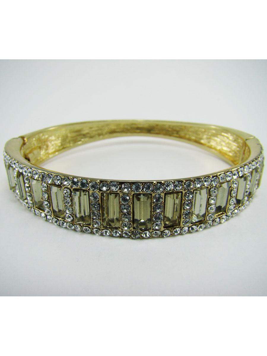 Браслет Taya, цвет: золотистый. T-B-7104T-B-7104Модный женский браслет Taya выполнен из металлического сплава с покрытием под золото и инкрустирован стразами. Изделие разъемной конструкции с пружинным механизмом имеет универсальный размер. Такой оригинальный браслет не оставит равнодушной ни одну любительницу изысканных и необычных украшений, а также дополнит повседневный или праздничный образ, подчеркнув достоинства женской ручки.