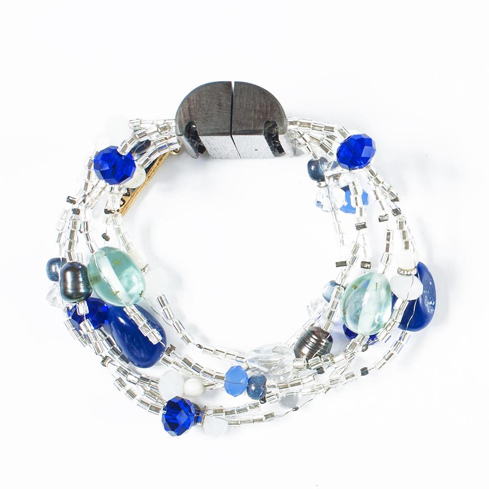 Браслет Selena Enigma, цвет: голубой, серый, синий. 4005482040054820Ювелирная смола, пальмовое дерево, искусственный жемчуг, бисер, кристаллы Preciosa. Гальваническое покрытие: золото, родий, длина браслета 22 см ширина 4 см