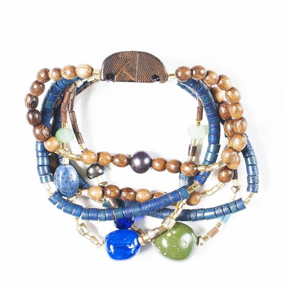 Браслет Selena Enigma, цвет: зеленый, коричневый, синий. 4005486040054860Пальмовое дерево, лазурит, ювелирная смола, искусственный жемчуг, бисер, кристаллы Preciosa. Гальваническое покрытие: золото, длина браслета 22 см ширина 3.5 см