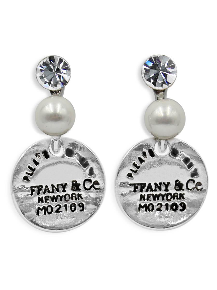 Серьги Taya, цвет: серебристый. T-B-12359T-B-12359-EARR-SILVERСерьги-гвоздики с заглушкой металл-пластик. С одной стороны скобы кристалл, с другой - мелкая жемчужина. Снизу подвижно крепится монетка с надписями. Размеры: длина 2,6 см, диаметр монетки 1,5 см.