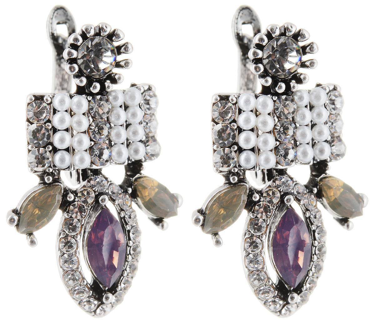 Серьги Taya, цвет: серебристый, пурпурный. T-B-12954T-B-12954-EARR-SL.PURPLEСерьги с английским замком. Некрупные, с мелкими деталями оформлены вставками из пастельных кристаллов. Много страз: есть блестящие, есть матовые белые. Металл в глубине слегка тонированный.