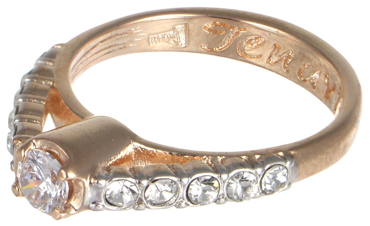 Кольцо Jenavi Teona. Энами, цвет: золотой. f428q0a0. Размер 17Коктейльное кольцоКольцо Jenavi Энами из коллекции Teona изготовлено из гипоаллергенного ювелирного сплава с позолотой и украшено чарующими фианитами.Дизайн этого кольца можно назвать элегантным и утонченным: классическая форма украшения будет хорошо смотреться на любой руке, а ряд сверкающих кристаллов по периметру аксессуара радует бесконечной красотой своих бликов. Изделие декорировано тиснением с названием коллекции изнутри.Если Вы находитесь в поиске аксессуара, который будет хорошо смотреться и в будние, и в праздничные дни, это кольцо - именно то, что Вам нужно! Классическая форма украшения легко впишется в офисный дресс-код, а блеск прозрачных фианитов будет уместен в любом праздничном образе