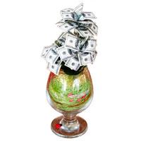 Денежное дерево 100 долларов89852Настольная композиция выполнена в виде миниатюрного денежного дерева. На пластиковое основание дерева насажены миниатюрные купюры-дубли достоинством в 100 долларов. Дерево закреплено в стеклянном бокале, оформленном искусственными листьями и различными декоративными элементами. На основании бокала расположена забавная божья коровка.
