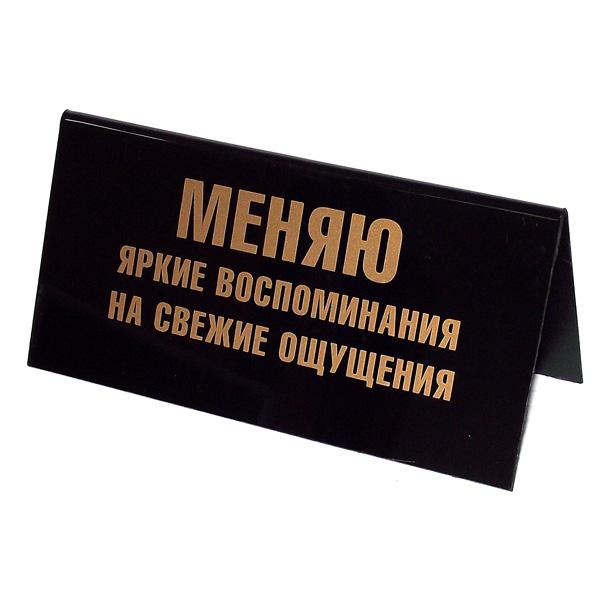 Табличка на стол Меняю яркие воспоминания на свежие ощущения / Рабочий день сокращает жизнь на 8 часов. 9454294542Табличка на стол, выполненная из пластика черного цвета, с одной стороны оформлена золотистой надписью: Меняю яркие воспоминания на свежие ощущения, а с другой - Рабочий день сокращает жизнь на 8 часов. Такая табличка забавно оформит ваш рабочий стол и вызовет улыбку у окружающих. Характеристики: Материал: пластик. Цвет: черный, золотистый. Размер таблички: 14 см х 5,5 см х 7 см. Артикул: 94542.