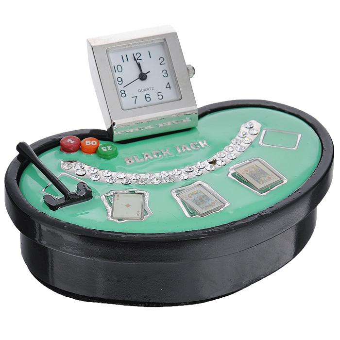 Часы настольные Покер, цвет: черный, зеленый. 2240822408Оригинальный дизайн настольных часов Покер разработан с учетом современных тенденций оформления интерьеров. Выполненные из металлического сплава в виде стола для игры в покер, эти часы, несомненно, будут привлекать к себе внимание. Часы с кварцевым механизмом работают плавно и бесшумно и требуют лишь примерно раз в год замены батарейки. На циферблате имеются часовая, минутная и секундная стрелки. Часы декорированы стразами. Такие часы легко впишутся в любой интерьер и станут великолепным подарком! Характеристики: Материал: металл (сплав цинка), стекло, стразы. Цвет: зеленый, черный. Размер часов: 8 см х 5 см х 3,5 см. Размер циферблата: 1,5 см х 1,5 см. Размер упаковки: 9,5 см х 5,5 см х 7 см. Артикул: 22408.