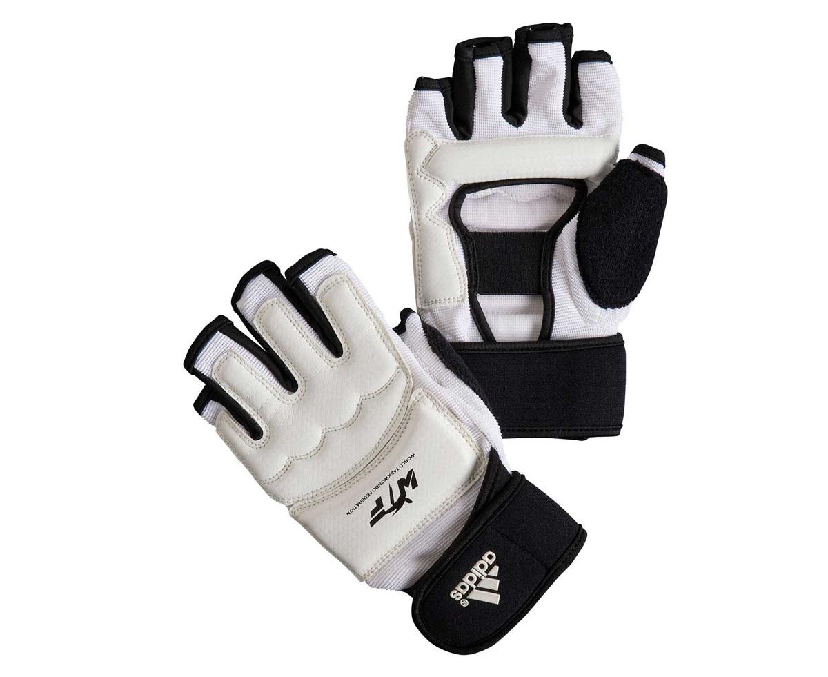 Перчатки для тхэквондо Adidas Fighter Gloves WTF, цвет: белый. Размер LadiTFG01Боевые перчатки Adidas Fighter Gloves предназначены для занятий тхэквондо и другими видами единоборств. Они отлично защищают суставы рук, но при этом не сковывают движения. В отличие от боксерских перчаток, они имеют обрезанные пальцы и открытую ладонь, что позволяет осуществлять захват. Перчатки Adidas Fighter Gloves WTF выполнены из искусственной кожи. Они обладают повышенной устойчивостью к изнашиванию. Перчатки прочно фиксируются на запястье широкой манжетой на липучке, что гарантирует быстроту и удобство одевания.