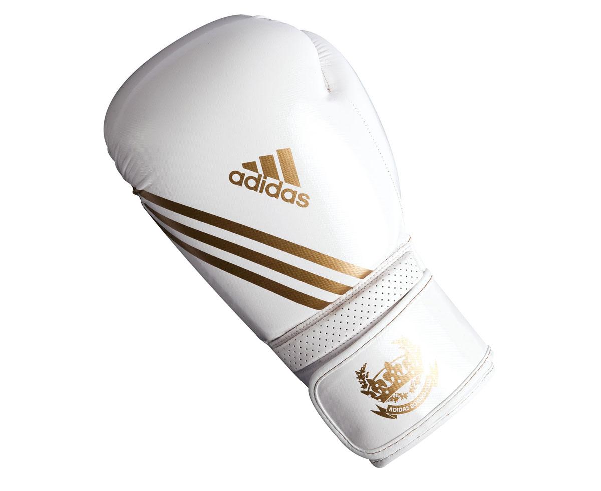 Перчатки боксерские Adidas Hybrid Aero Tech, цвет: бело-золотой. adiBL06. Вес 8 унцийadiBL06Боксерские перчатки Adidas Hybrid Aero Tech изготовлены из полиуретана PU4G, который по своим качествам не уступает натуральной коже. Внутренний наполнитель из многослойной пены закрывает тыльную сторону и боковую часть ладони, обеспечивая надежную защиту рук боксера и позволяя безопасно тренироваться в полную силу. Загнутый параллельно кулаку большой палец обеспечивает безопасность при нанесении ударов и защищает большой палец от вывихов и травм. Вентиляционные отверстия на ладони создают максимальный уровень комфорта для рук, поддерживая оптимальный микроклимат внутри перчаток. Широкий ремень, охватывая запястье, полностью оборачивается вокруг манжеты, благодаря чему создается дополнительная защита лучезапястного сустава от травмирования. Застежка на липучке способствует быстрому и удобному одеванию перчаток, плотно фиксирует перчатки на руке.