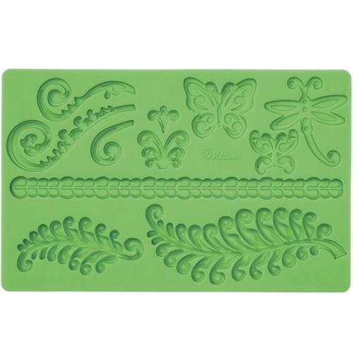 Молд для нанесения рисунка на мастику Wilton Папоротник и завитки, цвет: зеленый, 20 х 12,5 смWLT-409-2548Молд для нанесения рисунка на мастику Wilton Папоротник и завитки, выполненный из силикона, поможет вам легко нанести рисунки на мастику и сахарную пасту для тортов и сладких угощений. Молд содержит формы в виде бабочек, стрекоз и листьев папоротника. Использование и хранение: Перед первым использованием и после каждого применения вымойте молд в мыльной воде или на верхней полке в посудомоечной машине. Хорошо высушите молд перед использованием. Полезные советы по использованию: - Для того, чтобы мастика или цветочная паста не прилипали к молду, посыпьте его сахарной пудрой или смажьте растительным жиром сахарную мастику прежде чем накладывать на нее молд, - При раскатывании сахарной мастики используйте скалку для того, чтобы вся мастика была в полостях молда, - Следуйте инструкциям по изготовлению украшений, разместите их на торте, высушите. Изготовление: Скатайте сахарную мастику в трубочку такого же размера, как и ...