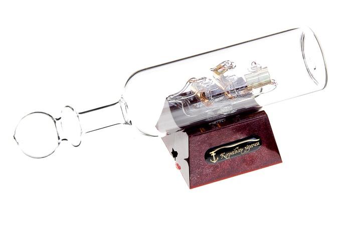 Корабль сувенирный в бутылке Корабль удачи, с подсветкой, длина 20 см. 295006UP210DFСувенирный корабль в бутылке Корабль удачи - прекрасный сувенир и великолепный элемент декора рабочей зоны в офисе или кабинете. В прозрачную бутылку помещена фигурка трехмачтового корабля с золотыми парусами. Для бутылки предусмотрена пластиковая подставка, украшенная надписью Корабль удачи. Стремящиеся в неизведанную даль, словно невесомые паруса заиграют по-новому, если вы включите яркую подсветку. Время идет, и мы становимся свидетелями развития технического прогресса, новых учений и практик. Но одно не подвластно времени - это любовь человека к морю и кораблям. Сувенирный корабль в бутылке наполнен историей и силой океанских вод. Данная модель кораблика станет отличным подарком для всех любителей морей, поклонников историй о покорении океанов и неизведанных земель. Модель корабля - подарок со смыслом. Издавна на Руси считалось, что корабли приносят удачу и везение. Поэтому их изображение и точные копии всегда присутствовали в помещениях. Удивите себя и своих близких необычным презентом. Подсветка работает от 3 батареек типа ААА (в комплект не входят). Длина бутылки: 20 см. Диаметр бутылки: 4,5 см. Размер подставки: 6,5 см х 6,5 см х 3,5 см.