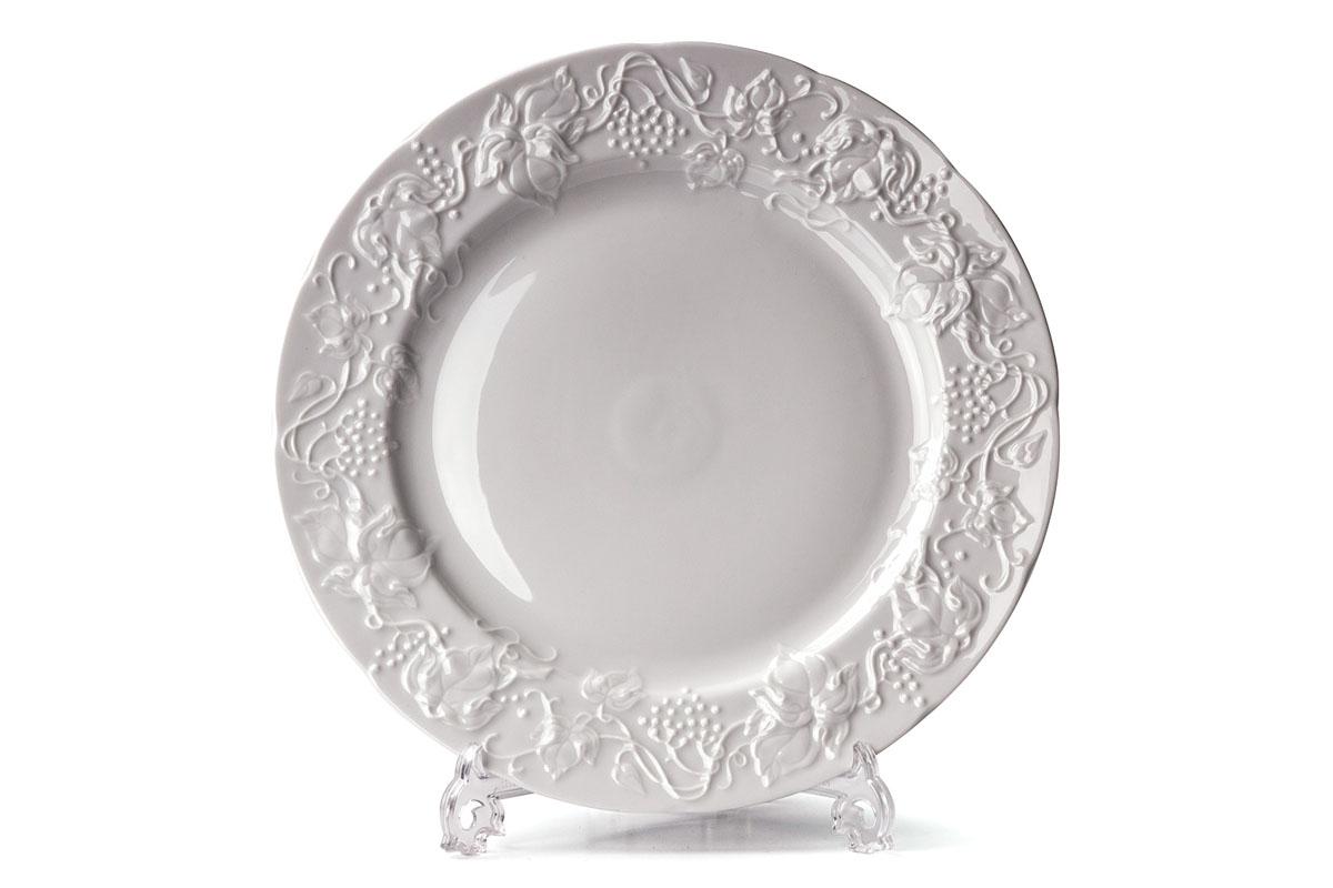 Тарелка обеденная La Rose Des Sables Vendanges, цвет: белый, диаметр 26 смVT-1520(SR)Обеденная тарелка La Rose Des Sables Vendanges - прекрасное дополнение праздничного стола. Изделие выполнено из высококачественного фарфора и украшено изысканным орнаментом. Фарфор марки La Rose Des Sables изготавливается из уникальной белой глины, которая добывается во Франции, в знаменитой провинции Лимож. Особые свойства этой глины, открытые еще в 18 веке, позволяют создать удивительно тонкую, легкую и при этом прочную посуду. Лиможский фарфор известен по всему миру. Это символ утонченности, аристократизма и знак высокого вкуса. Продукция импортируется в европейские страны и производится под брендом La Rose des Sables, что в переводе означает Роза песков. Преимущества этого фарфора заключаются в устойчивости к сколам и трещинам, что возможно благодаря двойному термическому обжигу. Посуда имеет маркировку Pate de Limoges, подтверждающую, что сырье для ее изготовления добыто именно в провинции Лимож, а качество соответствует европейским стандартам. Производство расположено в Тунисе. Коллекции бренда La Rose Des Sables самые разнообразные, от изделий в лаконичном и современном дизайне - отличный выбор на каждый день, до роскошной посуды с позолотой - для особого случая и праздничной сервировки стола. Диаметр тарелки: 26 см. Высота стенки: 2,5 см.