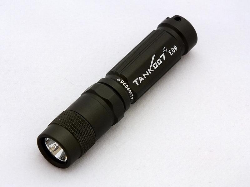 Фонарь светодиодный TANK007 E09, с комплектацией, цвет: графитE09GВысококачественный карманный светодиодный фонарь-брелок TANK007 E09 - самый компактный в своем классе. Фонарь выполнен из авиационного алюминия с III (наивысшей) степенью защитного анодирования корпуса. Водонепроницаемый — стандарт IPX8. Фонарь снабжен современным светодиодом CREE XP-E R3 (США) и встроенным стабилизатором напряжения. Особенности конструкции: - три режима работы фонаря: High (полная мощность), Medium (средний режим), Low (экономичный режим); - имеется функция памяти - при последующем включении фонарь начинает работать в выбранном ранее режиме; - включение и переключение режимов работы осуществляется вращением головной части фонаря - кратковременное вращение на четверть оборота вправо - влево до фиксации; - фонарь работает от одной батарейки ААА (в комплекте); - резиновое уплотнение в хвостовике фонаря; - при использовании светорассеивающего наконечника фонарь работает в режиме кемпинговой...