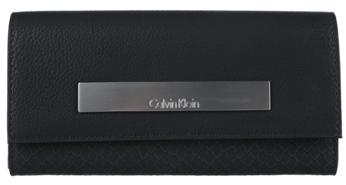 Кошелек женский Calvin Klein Jeans, цвет: черный. K60K601553_9100K60K601553_9100Элегантный кошелек Calvin Klein выполнен из искусственной кожи (полиуретана) с декоративным фактурным тиснением под кожу рептилии и оформлен металлической пластиной с гравировкой в названия бренда. Изделие закрывается клапаном на кнопку. Внутри кошелька расположены два отделения для купюр, отделение для монет на молнии, потайной кармашек и двенадцать карманов для пластиковых карт. Изделие поставляется фирменной упаковке. Практичный аксессуар прекрасно дополнит ваш образ.