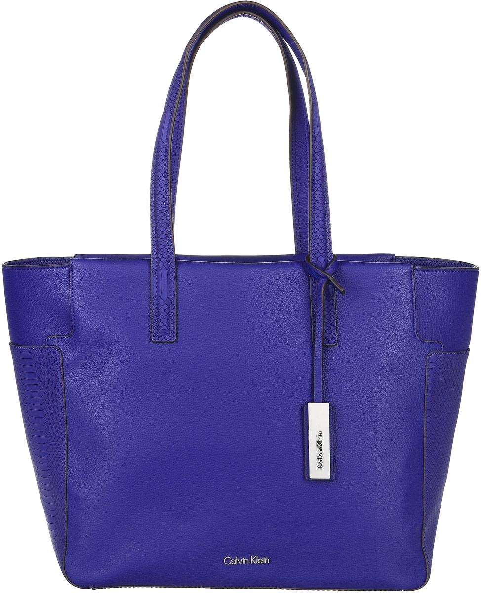 Сумка женская Calvin Klein Jeans, цвет: синий. K60K602240_4330K60K602240_4330Стильная сумка Calvin Klein не оставит вас равнодушной благодаря своему дизайну и практичности. Она изготовлена из качественного полиуретана и оформлена тиснением под рептилию. Лицевая сторона оформлена металлической пластинкой с названием бренда. Сумка оснащена удобными ручками, которые дополнены ремешком с фирменной металлической пластинкой. Изделие закрывается на удобную молнию. Внутри расположено одно вместительное отделение, которое содержит три открытых накладных кармана для телефона и мелочей и один вшитый карман на молнии. Такая модная сумка подчеркнет ваш неповторимый образ и займет достойное место в вашем гардеробе.