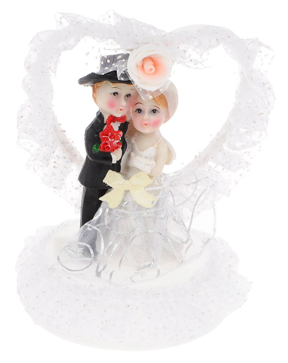 Фигурка декоративная Win Max Жених и невеста, высота 15 см27907Декоративная фигурка Win Max Жених и невеста изготовлена из полистоуна и текстиля. Изделие представляет собой круглую подставку с фигурками жениха и невесты, украшенных тесьмой и стразами. Такая фигурка идеально впишется в свадебный интерьер и будет радовать вас своим видом в самый важный день в вашей жизни. Высота фигурки: 15 см.