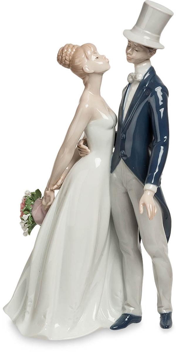 Статуэтка Pavone Молодожены. JP-15/33JP-15/33Статуэтка Молодожёнов высотой 30 см. Еще и надо было ждать пока разрешат поцеловать невесту… вот беспредел! Им еще неловко целоваться, особенно при большом скоплении людей. А на свадьбе это делать приходится. Стройная невеста в белом платье и молоденький жених во фраке и шляпе-цилиндре робко тянутся друг к другу губами, хотя он уже уверенно обнимает ее за талию. Об этих первых часах семейной жизни молодожены будут вспоминать всю свою жизнь, и такая вот фарфоровая фигурка останется долгой памятью об этом счастливом времени. Такую статуэтку можно не только на свадьбу подарить, но и по случаю помолвки. Главное, что это – пожелание семейного счастья, радостного отношения друг к другу и настоящей, искренней любви.