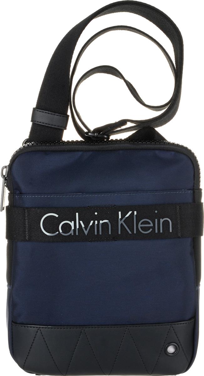 Сумка мужская Calvin Klein Jeans, цвет: темно-синий. K50K502291_4380656045562IV_390Стильная сумка Calvin Klein Jeans выполнена из полиуретана с добавлением полиамида и полиэстера. Изделие содержит одно большое отделение, которое закрывается на застежку-молнию. Внутри сумки размещен один кармашек на застежке-молнии. Спереди сумка также дополнена накладным карманом на застежке-липучке. Модель оснащена плечевым ремнем регулируемой длины.