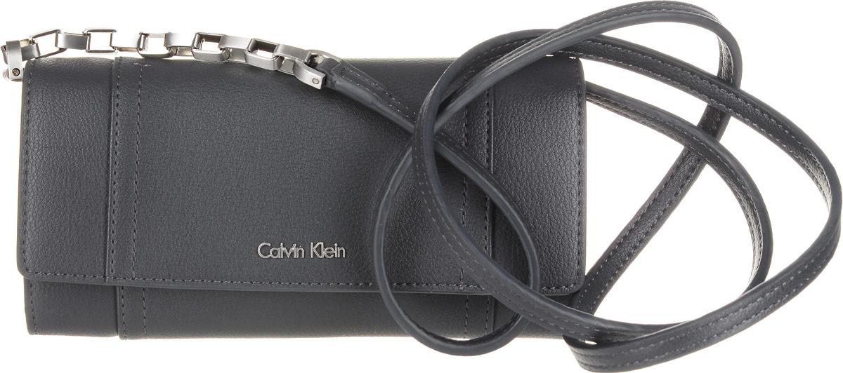 Кошелек женский Calvin Klein Jeans, цвет: черный. K60K602432_0040K60K602432_0040Элегантный кошелек Calvin Klein Jeans выполнен из искусственной кожи (полиуретана) и оформлен металлической пластиной с названием бренда. Изделие закрывается клапаном на кнопку. Внутри кошелька расположены четыре отделения для купюр, отделение для монет на молнии, потайной кармашек и двенадцать карманов для пластиковых карт. На задней стороне изделия имеется прорезной карман на застежке-молнии. Дополнена модель плечевым ремнем.