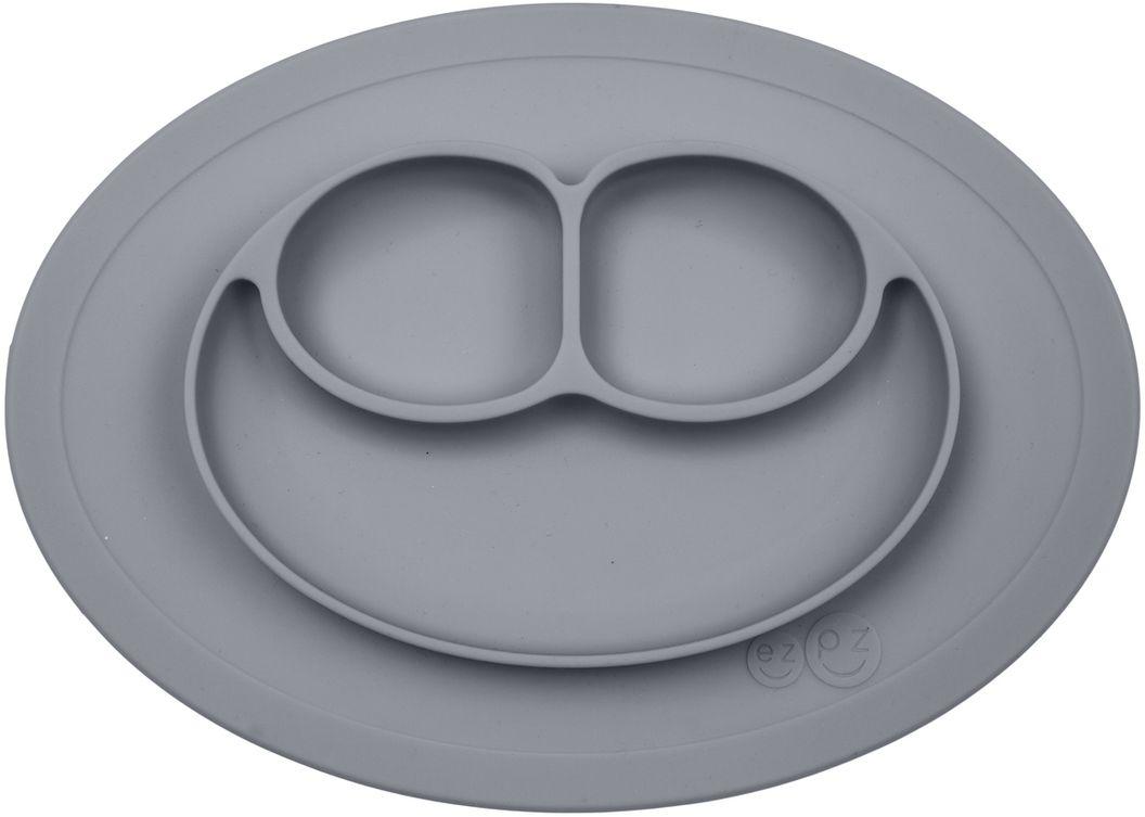Ezpz Тарелка детская Mini Mat цвет серый115510Ezpz Mini Mat - уменьшенная версия тарелочки-плейсмата Happy Mat. Предназначена для столиков для кормления и использования в поездках. Рекомендована для малышей от 4 месяцев. Тарелка тоньше, легче и компактнее, чем Happy Mat, но обладает теми же отличительными чертами: присасывается к столу, чтобы ребенок не смог ее перевернуть; подходит для микроволновки и посудомоечной машины; улыбается и вызывает у детей улыбку. Вмещает 240 мл. У тарелочки также есть удобный чехольчик с ручками, который легко можно взять с собой.Тарелка разработана и запатентована в США. Идея создания удобной безопасной посуды для детей принадлежит многодетной маме, которая как никто другой знает, как сложно уследить за детками во время еды и сохранить при этом чистоту и порядок. Благодаря такой тарелочке прием пищи становится веселым и безопасным, а кухня остается чистой и опрятной.