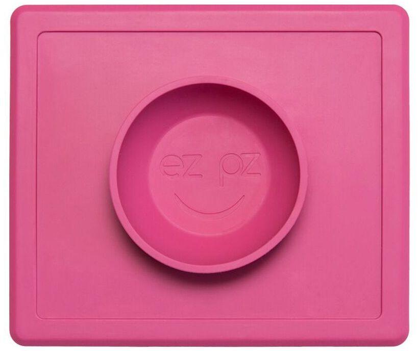 Ezpz Тарелка детская Happy Bowl цвет розовый9832AQEzpz Happy Bowl - силиконовая тарелка-плейсмат, которую невозможно перевернуть. Чаша высотой почти 4 см и объемом 240 мл идеально подходит для завтраков и обедов. Область плейсмата не дает ребенку испачкать стол. Тарелка изготовлена из силикона высочайшего качества и абсолютно безопасна. Не имеет липучек или присосок - фиксация происходит на любой ровной горизонтальной поверхности за счет плоской, гладкой поверхности тарелочки - мата. Подходит для использования в микроволновке и посудомоечной машине. Выглядит как улыбающаяся рожица, что очень нравится детям и их мамам. Тарелка разработана и запатентована в США. Идея создания удобной, безопасной посуды для детей принадлежит многодетной маме, которая как никто другой знает, как сложно уследить за детками во время еды и сохранить при этом чистоту и порядок. Благодаря такой тарелочке прием пищи становится веселым и безопасным, а кухня остается чистой и опрятной.