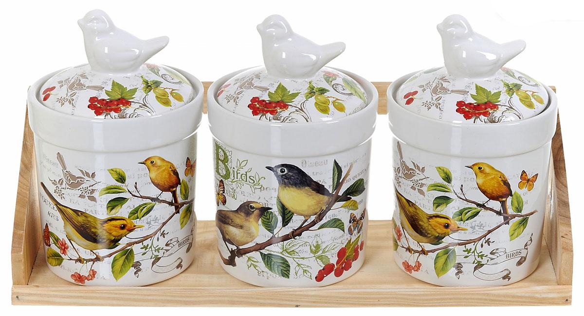 Набор банок для сыпучих продуктов Polystar Birds, 4 предметаL2430756Набор Polystar Birds состоит из трех банок для сыпучих продуктов и деревянной подставки. Изделия выполнены из прочной доломитовой керамики высокого качества. Гладкая и ровная глазурованная поверхность обеспечивает легкую очистку. Изделия декорированы красочным рисунком. Такие банки прекрасно подойдут для хранения различных сыпучих продуктов: специй, чая, кофе, сахара, круп и многого другого. Крышка плотно прилегает к стенкам емкости. Можно использовать в микроволновой печи, в холодильнике и посудомоечной машине. Диаметр банки: 10 см. Высота банки: 15,5 см. Объем банки: 500 мл.