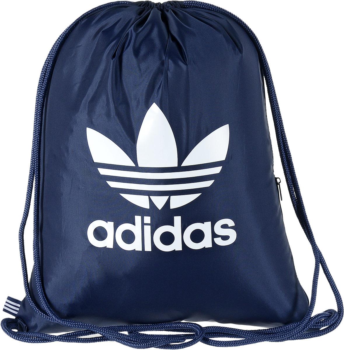 Рюкзак спортивный Adidas Trefoil, цвет: темно-синий, 23 л. BK67270054558 ТаймырСтильный спортивный рюкзак Adidas Trefoil выполнен из полиэстера и оформлен символикой бренда. Изделие имеет одно основное отделение, которое закрывается с помощью затягивающего шнурка. С внутренней стороны изделие оснащено удобной ручкой для переноски. Снаружи, с одной из боковых сторон находится прорезной карман на застежке-молнии. Веревочные завязки можно использовать как наплечные лямки. Стильный и функциональный рюкзак поместит все необходимое.