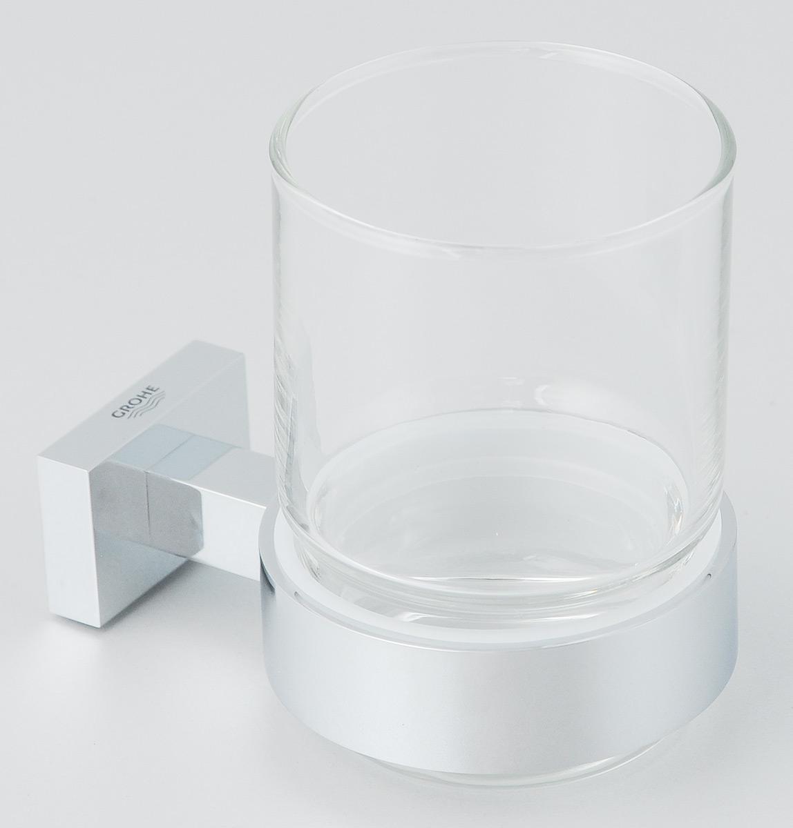 Стакан Grohe Essentials Cube, с держателем40755001Стакан с держателем Grohe Essentials Cube очень практичен и функционален. Стакан выполнен из толстого стекла. Держатель изготовлен из металла с хромированным покрытием. Благодаря специальной технологии Grohe StarLight покрытие обеспечивает сияющий блеск на протяжении всего срока службы. Кроме того, оно отталкивает грязь, не тускнеет и обладает высокой степенью износостойкости. Стакан крепится к стене (крепежные элементы поставляются в комплекте). Крепление скрытое. Благодаря неизменно актуальному дизайну и долговечному хромированному покрытию, такой стакан отлично дополнит интерьер ванной комнаты, воплощая собой изысканный стиль и превосходное качество. Диаметр стакана: 7 см. Высота стакана: 9,5 см. Размер (с держателем): 11 х 7 х 9,5 см.