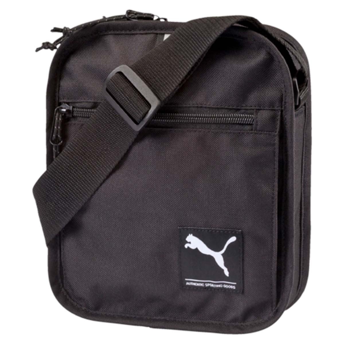 Сумка городская Puma Academy Portable, цвет: черный. 072991013-47670-00504Стильная сумка Puma Academy Portable, созданная из практичного полиэстера с изнанкой из полиуретана - это удобная сумка для всех необходимых вещей. Сумка оснащена двусторонней застежкой главного отделения, карманом для мелочей спереди, а также регулируемой по длине лямкой для ношения через плечо. С этой сумкой вы будете заметны в темное время суток, так как по периметру сумка отделана светоотражающей тесьмой, а также отражающие волокна добавлены в шнур застежки. Застежки-молнии оснащены брендированными язычками.