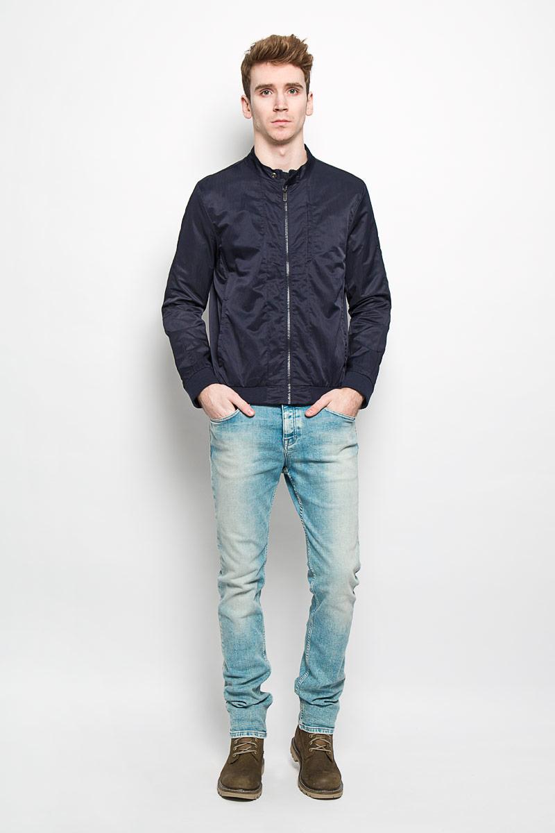 Ветровка130227-0053Стильная мужская куртка Calvin Klein Jeans, рассчитанная на прохладную погоду, поможет вам почувствовать себя максимально комфортно. Модель прямого кроя изготовлена из полиэстера с добавлением нейлона. Модель с подкладкой из полиэстера с перфорацией, застегивается по всей длине на пластиковую застежку-молнию. Вырез горловины дополнен небольшим воротником-стойкой, который застегивается на хлястик с кнопкой. Манжеты и низ изделия выполнены трикотажной резинкой, обеспечивая наилучшую защиту от ветра и холода. Модель дополнена прорезным карманом на кнопке на груди, а также двумя боковыми карманами на кнопках. С внутренней стороны изделия предусмотрен открытый карман. Куртка декорирована логотипом бренда на левом рукаве. Стильная и легкая куртка займет достойное место в вашем гардеробе. Модная фактура ткани, отличное качество, великолепный дизайн.