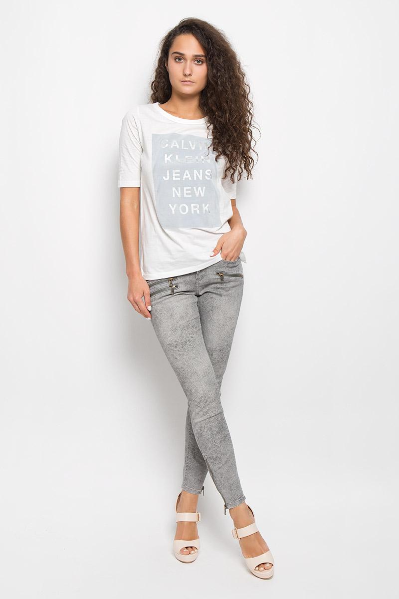ФутболкаSKL2040JRМодная женская футболка Calvin Klein Jeans изготовлена из натурального хлопка. Материал изделия очень мягкий, тактильно приятный, не сковывает движения и хорошо пропускает воздух, обеспечивая комфорт при носке. Футболка с круглым вырезом горловины и короткими рукавами имеет прямой силуэт. Вырез горловины оформлен двойной окантовкой. По бокам имеются маленькие разрезы. Изделие украшено вставкой с бархатистой поверхностью, дополненной надписью. Высокое качество, актуальный дизайн и расцветка придают изделию неповторимый стиль и индивидуальность. Футболка займет достойное место в вашем гардеробе!