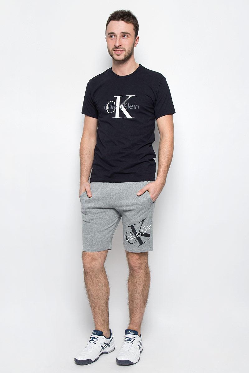 ШортыNM1269E_2GYМужские шорты Calvin Klein Underwear выполнены из хлопка с добавлением полиэстера. Модель по поясу дополнена эластичной резинкой и шнурком-кулиской для лучшей посадки изделия по фигуре. В боковых швах обработаны втачные карманы. Шорты оформлены термоаппликацией в виде названия бренда.