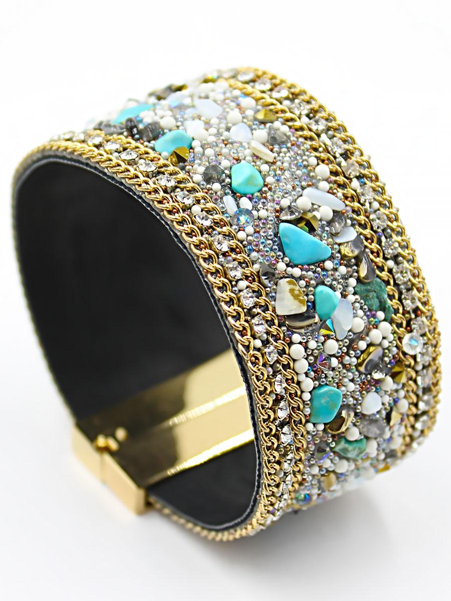 Браслет женский Taya, цвет: золотистый, бирюзовый. T-B-11961T-B-11961-BRAC-GL.TURQБраслет с магнитной застежкой собрано в технике алмазной мозаики, что придает изделию определенную фактуру и рельеф. Модель декорирована цепями, бусинами, стразами, камнями и шипами.